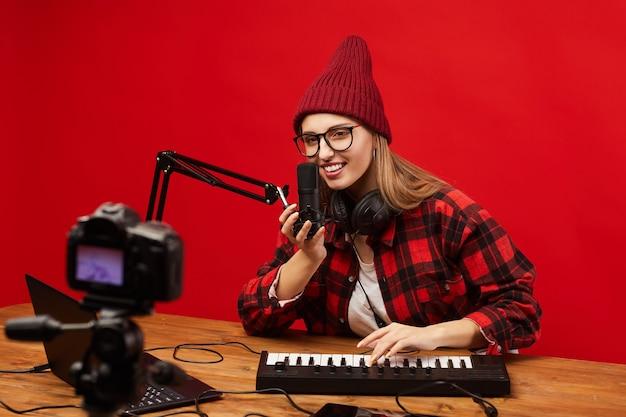 Молодой блоггер сидит за столом, играет на музыкальной клавиатуре и поет в микрофон, она снимает видео для своих подписчиков