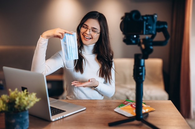 Young blogger smiling female is filming her vlog and showing her audience to be safe and use medical mask. coronovirus safe workplace concept.