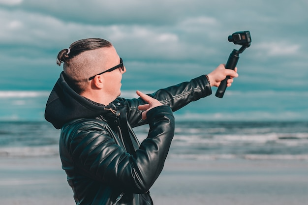 Young blogger in sunglasses making selfie or streaming video at the beach using action camera with gimbal camera stabilizer.