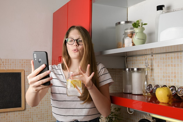 Young blogger talking to a phone camera, doing a live on social media showing a drink while sitting on the kitchen table