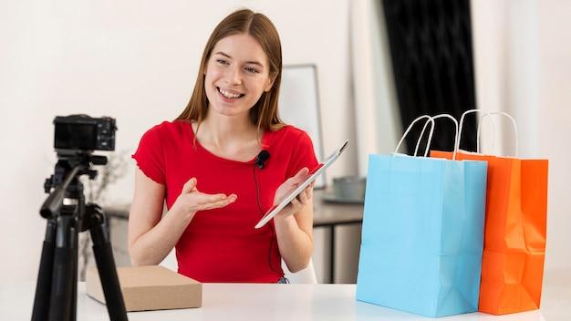 カメラでショッピングを開梱する若いブロガー