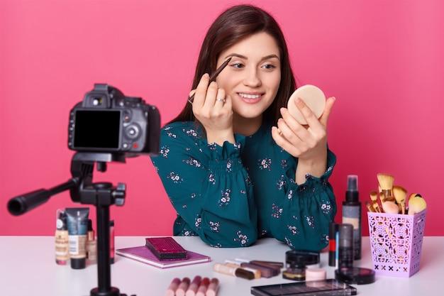 Молодой блогер, носит стильную блузку, красивая девушка сидит перед цифровым фотоаппаратом, учит своих последователей