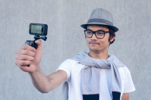 Young blogger with a hat and glasses, shoots a vlog video on an action camera.