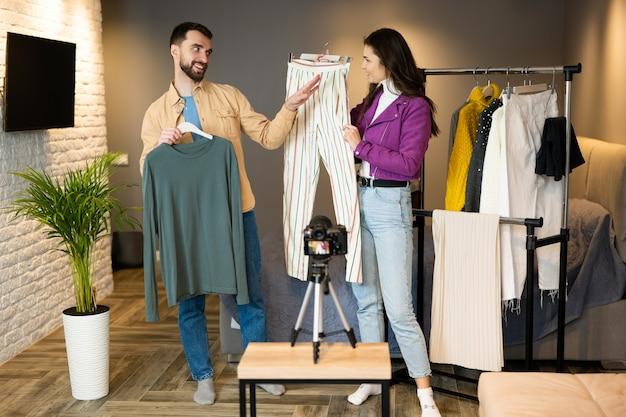 Молодые блогеры, друзья парня и девушки, показывают одежду своим подписчикам в социальных сетях, чтобы продавать ее в интернете