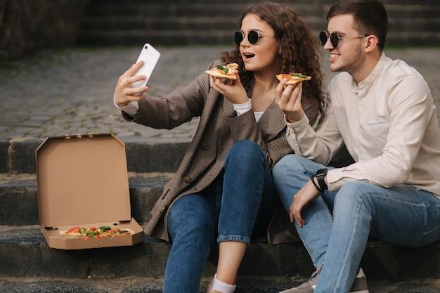 Молодые блогеры делают селфи с кусочком пиццы в руках