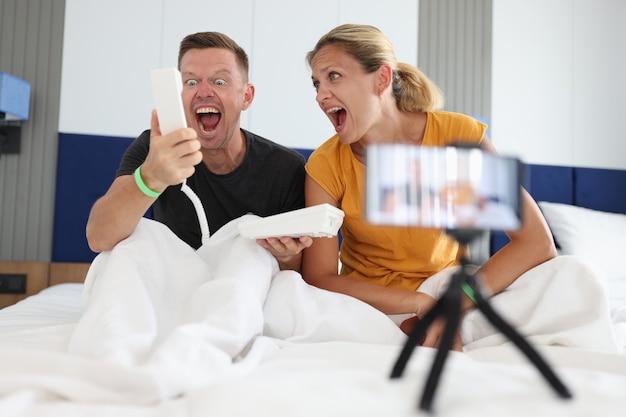 若いブロガーの男性と女性がホテルの部屋の不適切な行動で受話器に叫ぶ
