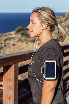 音楽を聴いている彼女の腕にヘッドフォンと携帯電話を持つ若い金髪アスリート女性