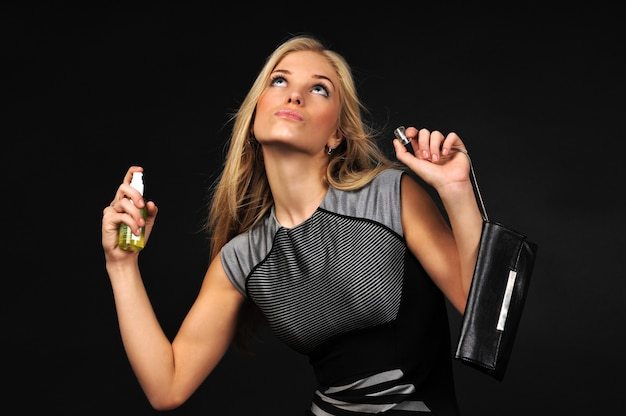 Young blond beautiful woman in dress perfuming herself