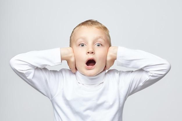 Молодой блондин мальчик закрывает уши
