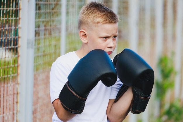 Молодой белокурый мальчик в белой футболке с боксерскими перчатками. фото высокого качества