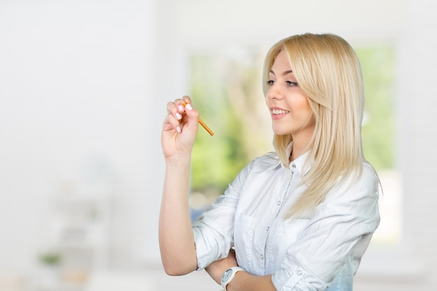 Young blond businesswoman writing on the touchscreen