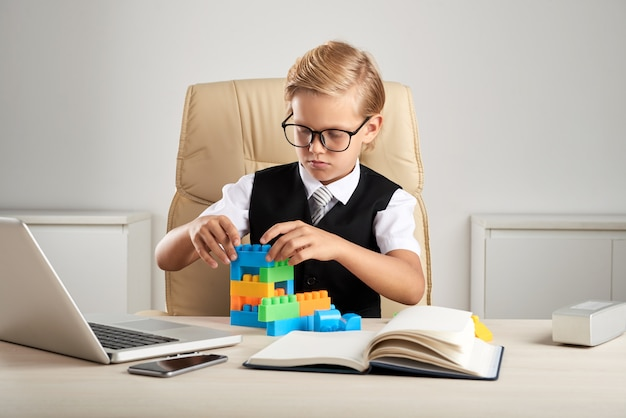 Young blond caucasian boy sitting in executive chair in office and playing with building blocks