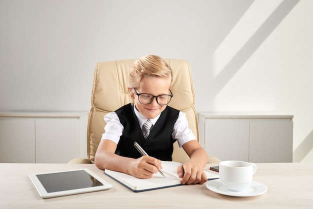 Young blond caucasian boy sitting in executive chair in office and writing in journal