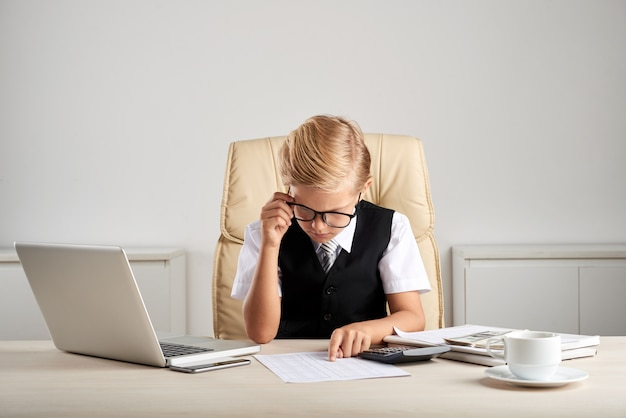 Young blond caucasian boy sitting at executive desk in office and studying documents
