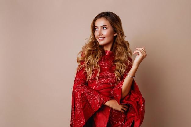Giovane donna bionda celebra in lussuoso abito rosso con maniche ampie. umore di capodanno.