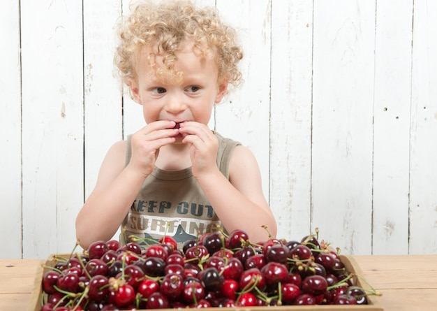 A young blond curly boy eating cherries
