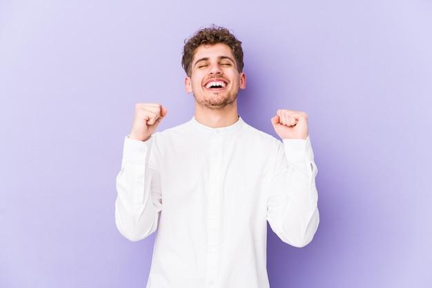 勝利、情熱的な熱意、幸せな表情を祝って分離された若い金髪巻き毛白人男性。