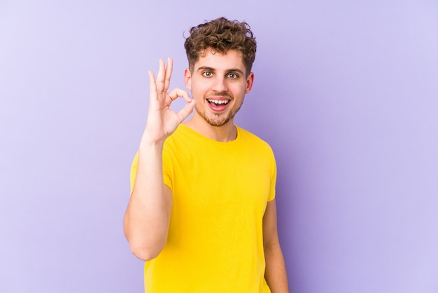 Young blond curly hair caucasian man isolated cheerful and confident showing ok gesture.