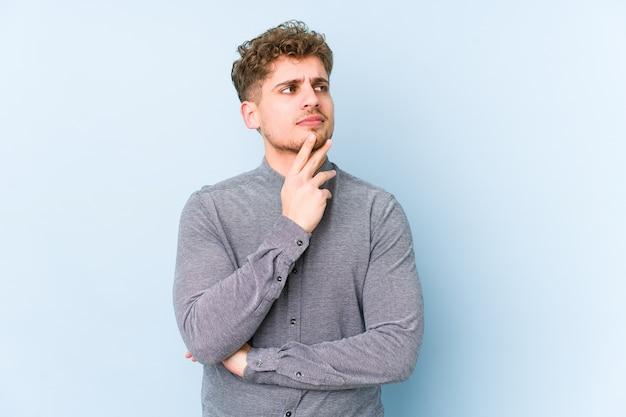 Молодой кавказский мужчина со светлыми вьющимися волосами изолировал созерцание, планирование стратегии, думая о способе ведения бизнеса.