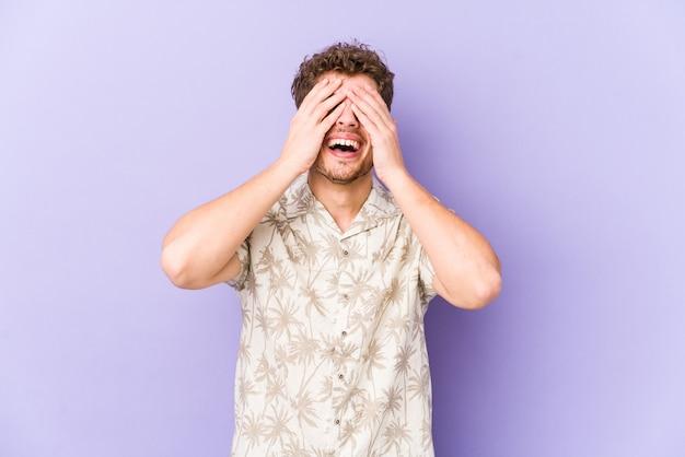 Молодой кавказский мужчина со светлыми вьющимися волосами изолированно закрывает глаза руками, широко улыбается, ожидая сюрприза.