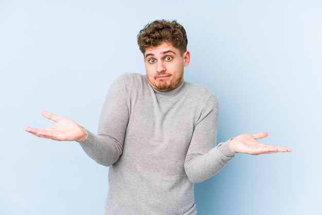 Young blond curly hair caucasian man isolated doubting and shrugging shoulders in questioning gesture.