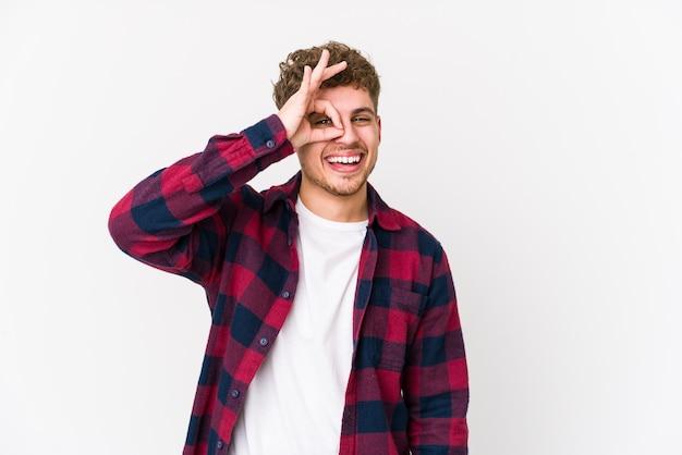 若いブロンドの巻き毛の白人男性は、目に大丈夫なジェスチャーを保ちながら興奮して孤立しました。