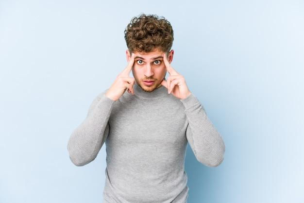 孤立した若い金髪巻き毛の白人男性は、人差し指を頭に向けたまま、タスクに焦点を当てました。