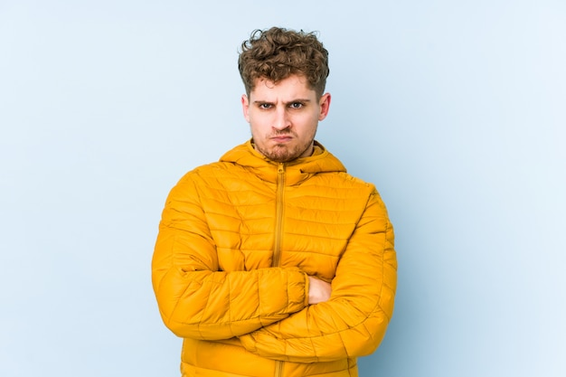Young blond curly hair caucasian man isolated frowning face in displeasure, keeps arms folded.