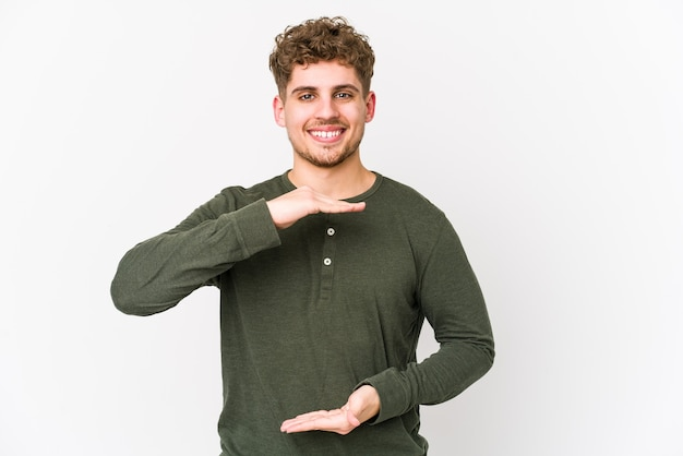 Young blond curly hair caucasian man isolated holding something with both hands, product presentation.