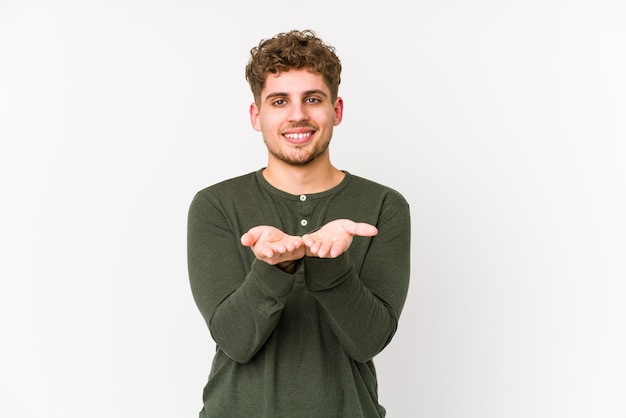 Young blond curly hair caucasian man isolated holding something with palms
