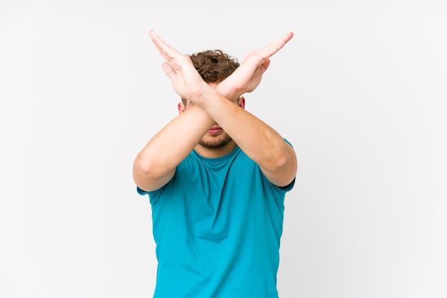 Молодой кавказский мужчина со светлыми вьющимися волосами изолирован, скрестив две руки
