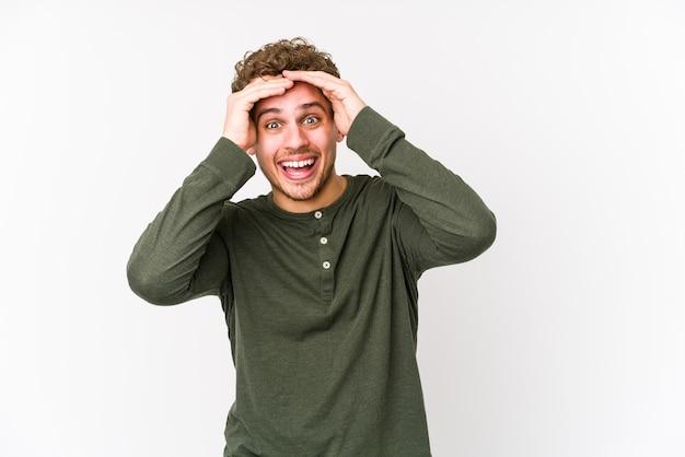 Молодой кавказский мужчина белокурых вьющихся волос изолирован, радостно смеется, держа руки на голове. концепция счастья.
