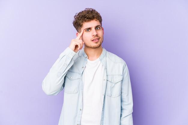 Молодой кавказский человек со светлыми вьющимися волосами изолировал указывая висок пальцем, думая, сосредоточенный на задаче.