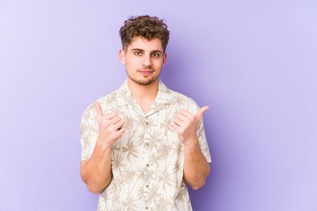 若いブロンドの巻き毛の白人男性は、両方の親指を上げて、笑顔で自信を持って分離しました。