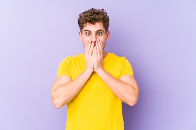 Young blond curly hair caucasian man isolated shocked covering mouth with hands.