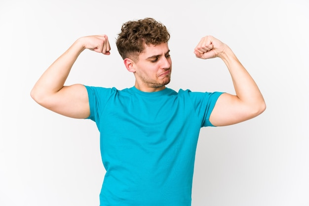 Young blond curly hair caucasian man isolated showing strength gesture with arms, symbol of feminine power