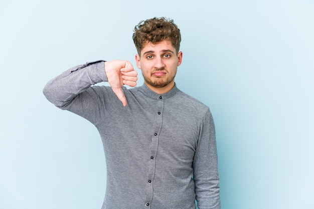Young blond curly hair caucasian man isolated showing thumb down