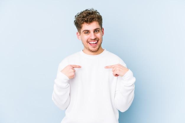 若いブロンドの巻き毛の白人男性分離驚いて指で指している、広く笑っています。