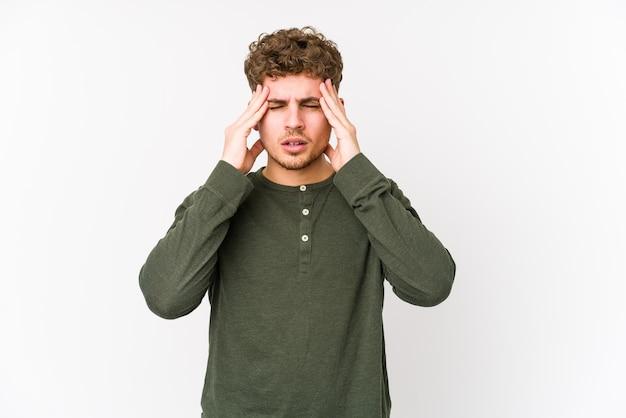 若いブロンドの巻き毛の白人男性は、こめかみに触れて頭痛を持って孤立しました。
