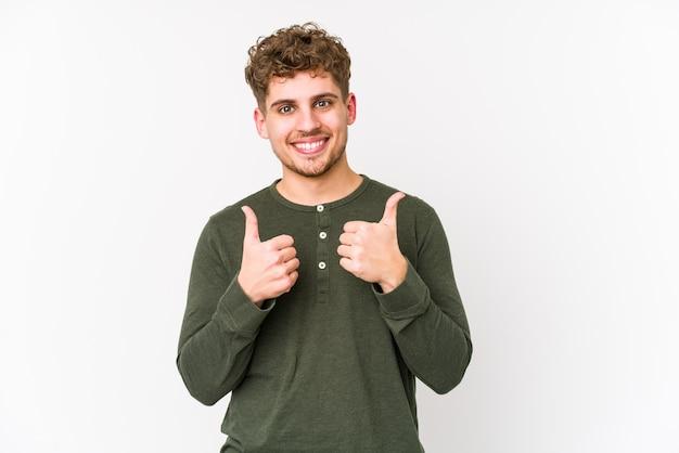 両方の親指を上げて、笑顔で自信を持って若い金髪巻き毛白人男。