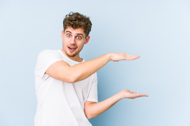 Young blond curly hair caucasian man shocked and amazed holding a blank space between hands.