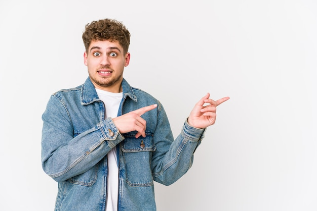 Young blond curly hair caucasian man shocked pointing with index fingers to a blank space.