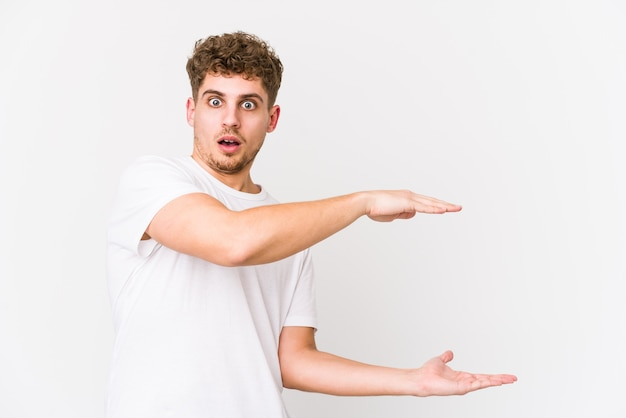 Young blond curly hair man isolated shocked and amazed holding a copy space between hands
