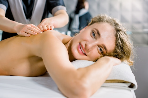 Young blond curly woman receiving classic manual back massage in medical spa center