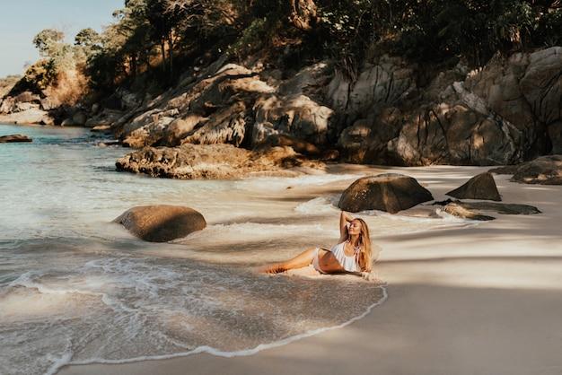 ビーチで白いビキニ水着を着た若い金髪のヨーロッパの女性は、砂浜の海に横たわっています。
