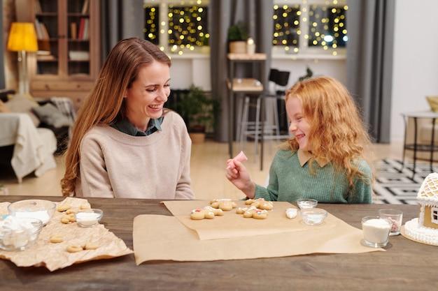 젊은 금발 여성과 그녀의 귀여운 딸 수제 진저 쿠키에 웃고