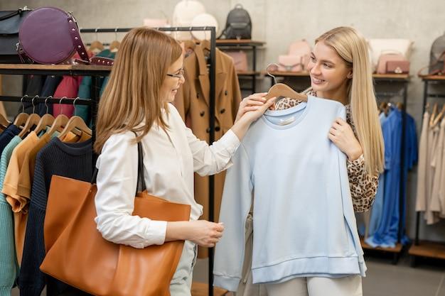 Молодая блондинка консультируется с мамой, показывая свою белую толстовку среди стоек с новыми модными коллекциями в бутике