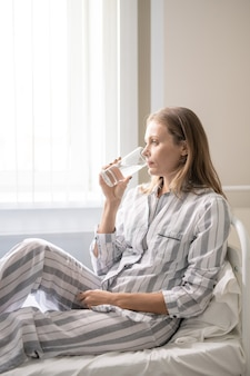 ベッドに座って、コップ一杯の水を持っているか、錠剤を服用している縞模様のパジャマで現代のcovid病院の若い金髪の女性患者