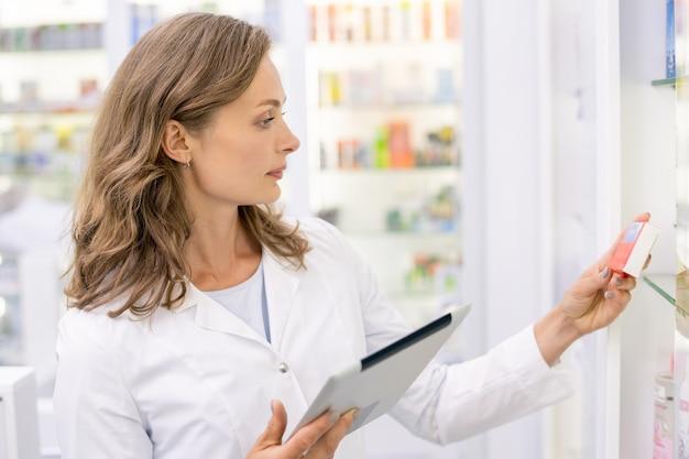 ドラッグストアで働いている間、赤い箱の新しい薬についての情報を学ぶデジタルタブレットを持つ若い金髪の女性薬剤師