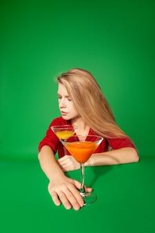緑の背景にパーティー中にカラフルなカクテルとメガネの近くに横たわって目を閉じて若い金髪の女性